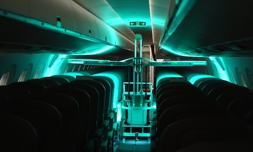 A robot disinfects an airplane interior.